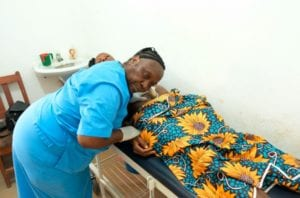 A traditional birth attendant at Wellbody Clinic in Kono, checks on a pregnant patient