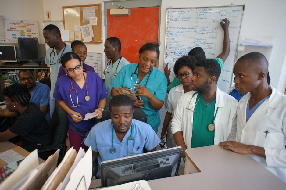 Doctors and medical staff gather around a computer discussing patient notes