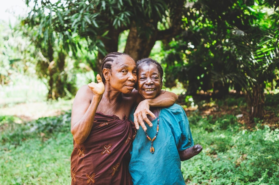 Kumba Gbetu, who lost both her hands during the civil war in Sierra Leone, with a friend