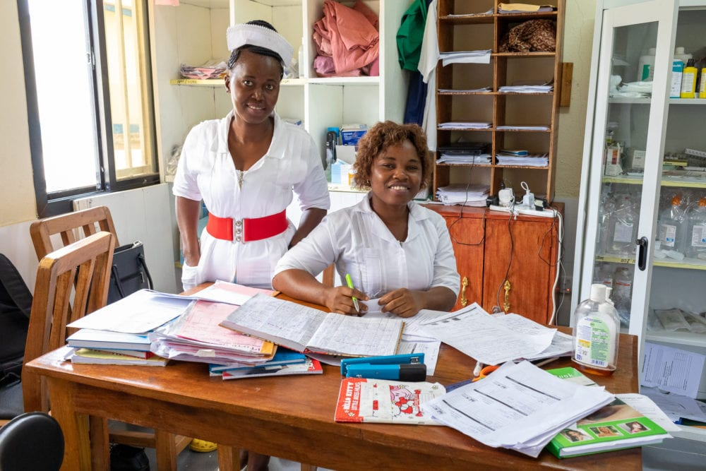 Two staff at Koidu Government Hospital complete paperwork for patients in the new emergency ward