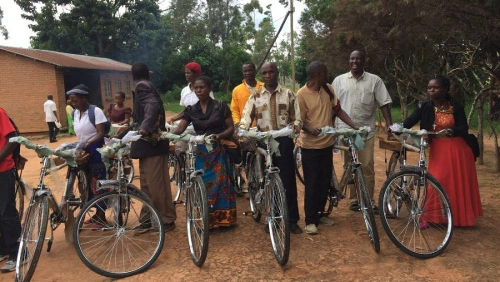 PIH staff and community health workers stand with their new bicycles