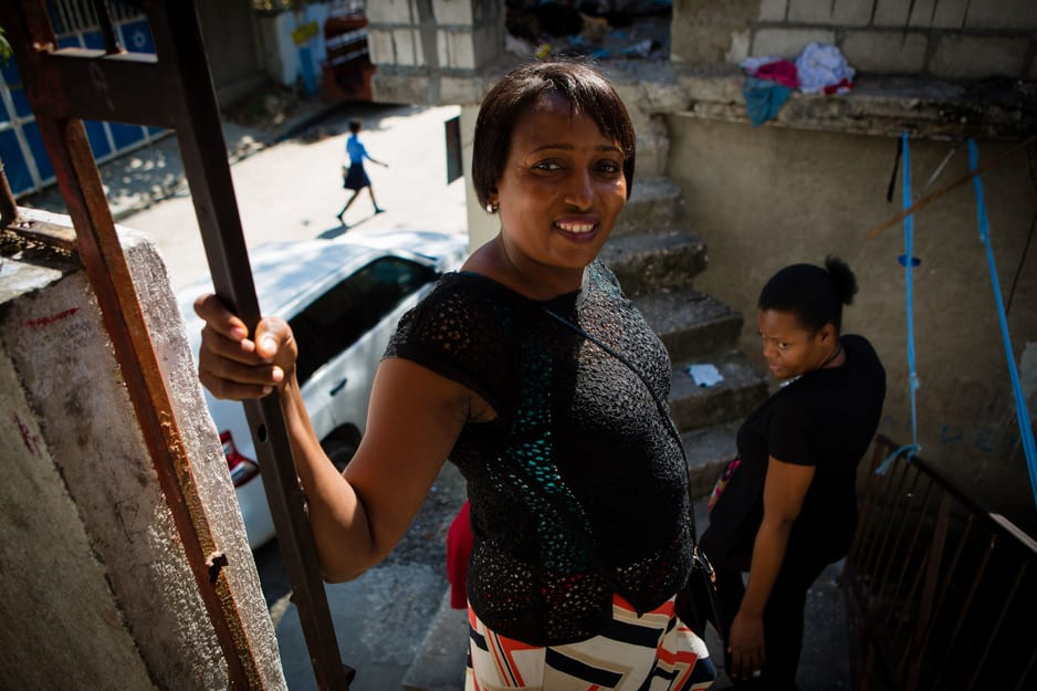 Oldine Deshommes walks down a set of stairs after visiting the home of a breast cancer patient in Haiti