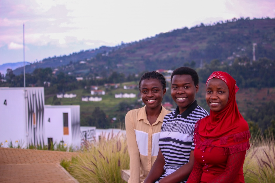 Three female students sit smiling outside at the University of Global Health Equity UGHE campus