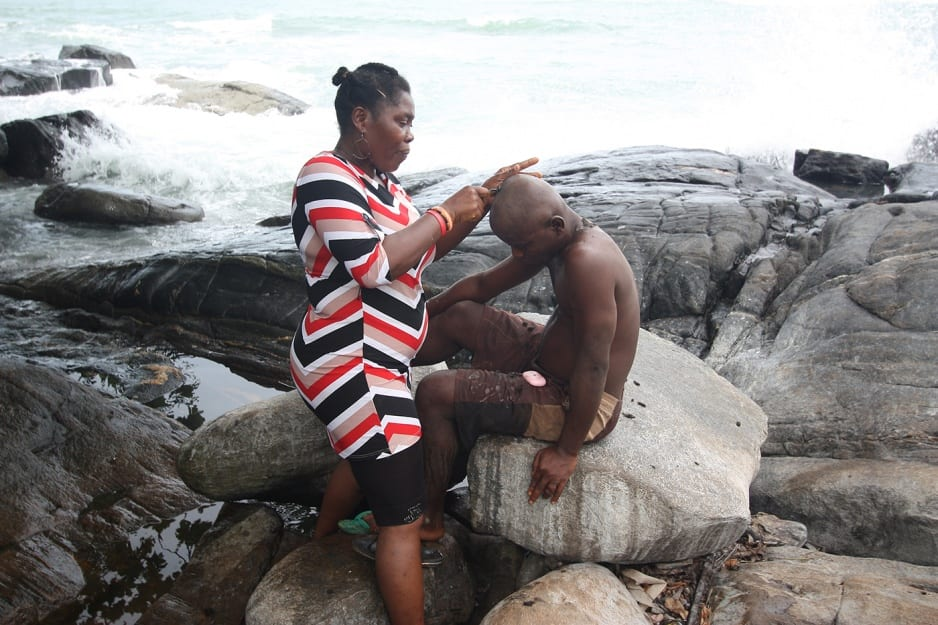 The PIH mental health program coordinator cuts the hair of a patient by the river in Harper, Liberia