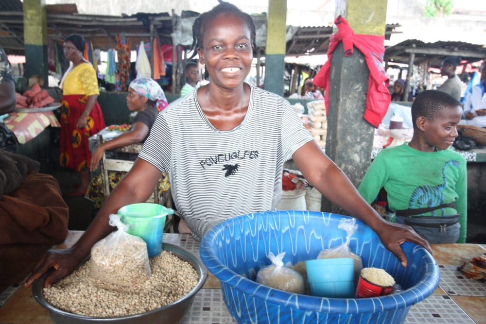 A woman stands at a crowded market selling rice