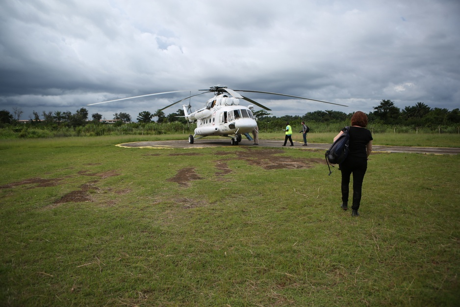 Dr. Sheila Davis walks towards a helicopter in the middle of a field