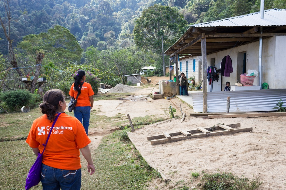 Two PIH community health workers walk towards a house for a home visit in Mexico