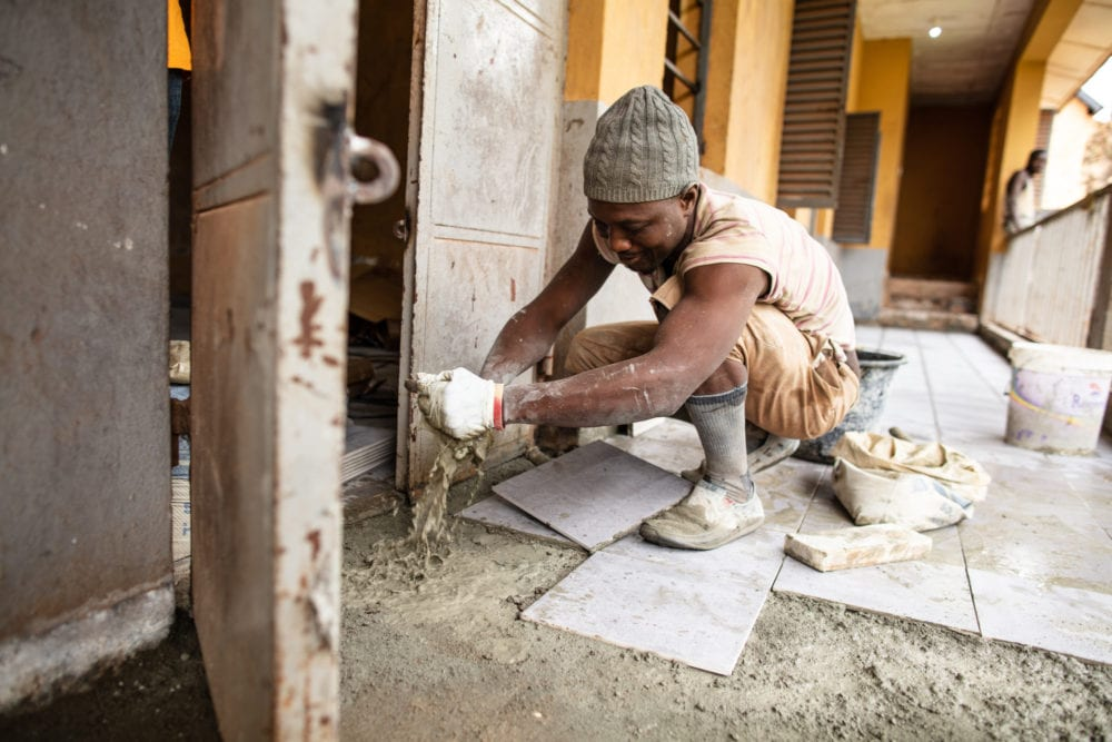 A construction worker repairs Sierra Leone Psychiatric Hospital