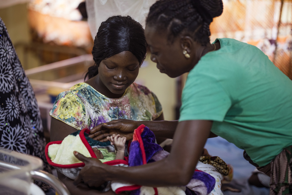A staff member assists a new mother holding her child