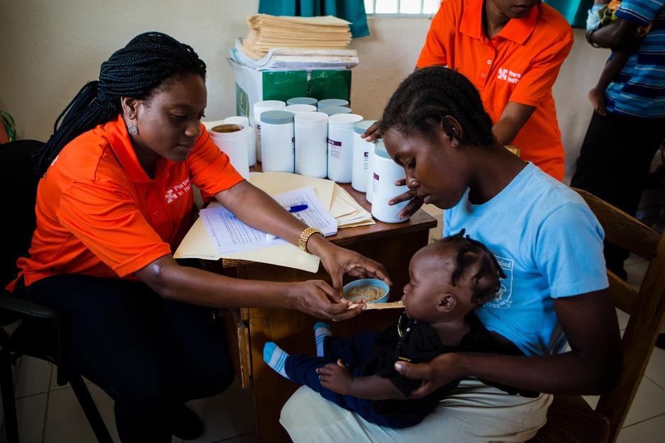 A PIH nurse feeds a child Nourimanba