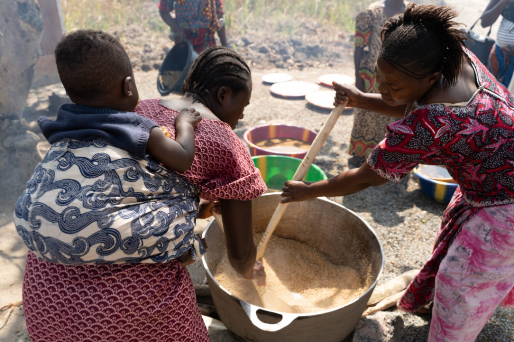 Two women work together to mix rice, fish and Bennimix in a large pot