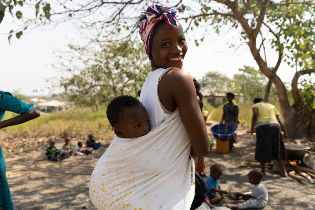 A mother stands with her child on her back at a MAM event in Sierra Leone