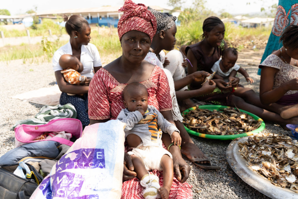 Women sit preparing food, many with children on their laps