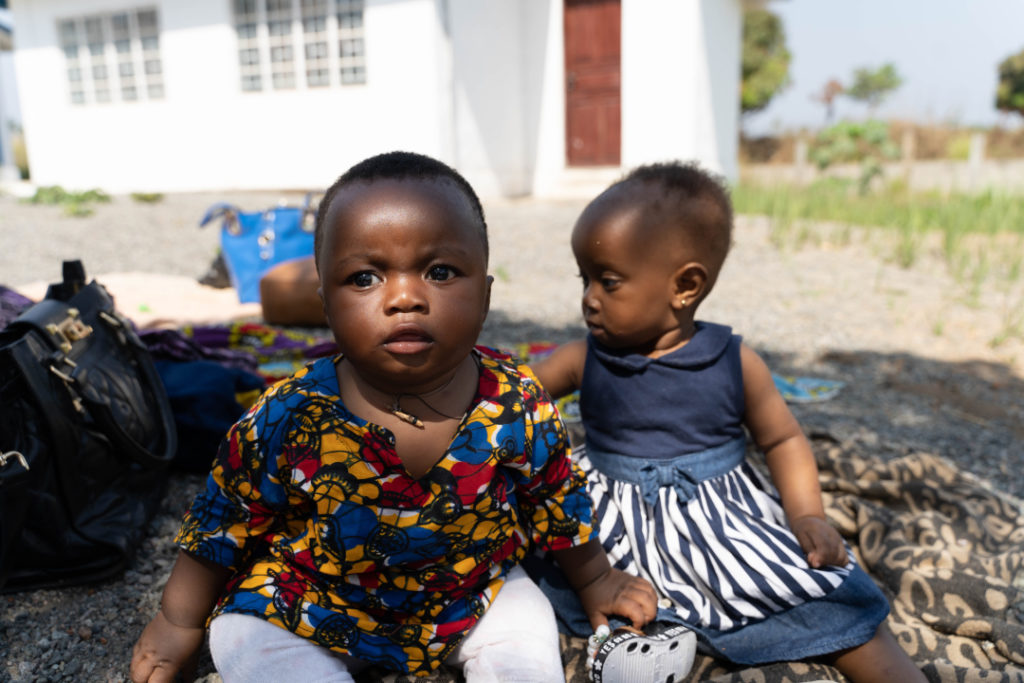 Two young children sit together in the shade at a MAM event in Kono, Sierra Leone