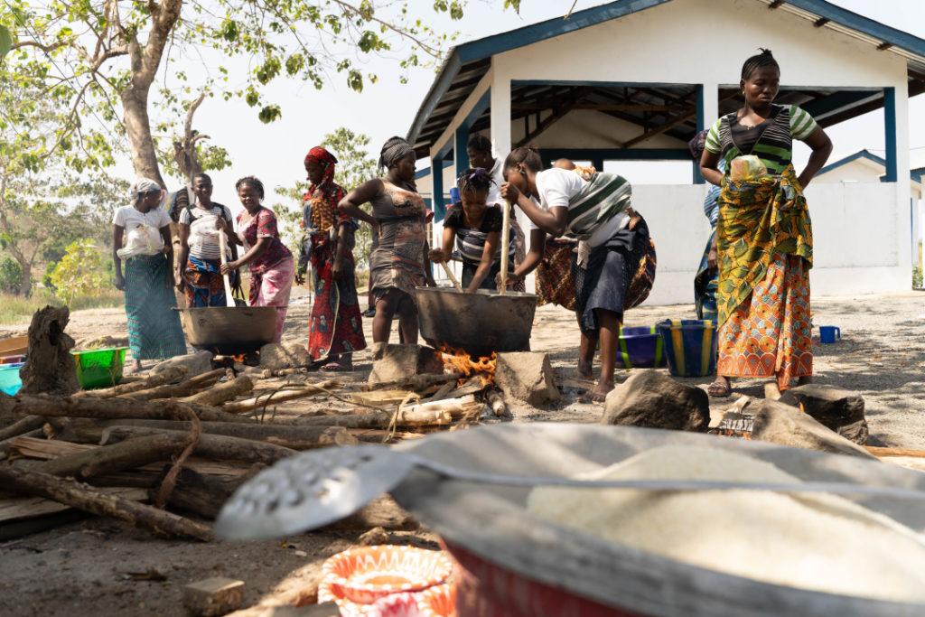 Women cook together outside Wellbody clinic in Sierra Leone