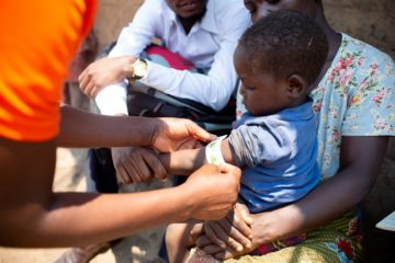 A PIH staff member measures the mid-upper arm circumference of 3-year-old child