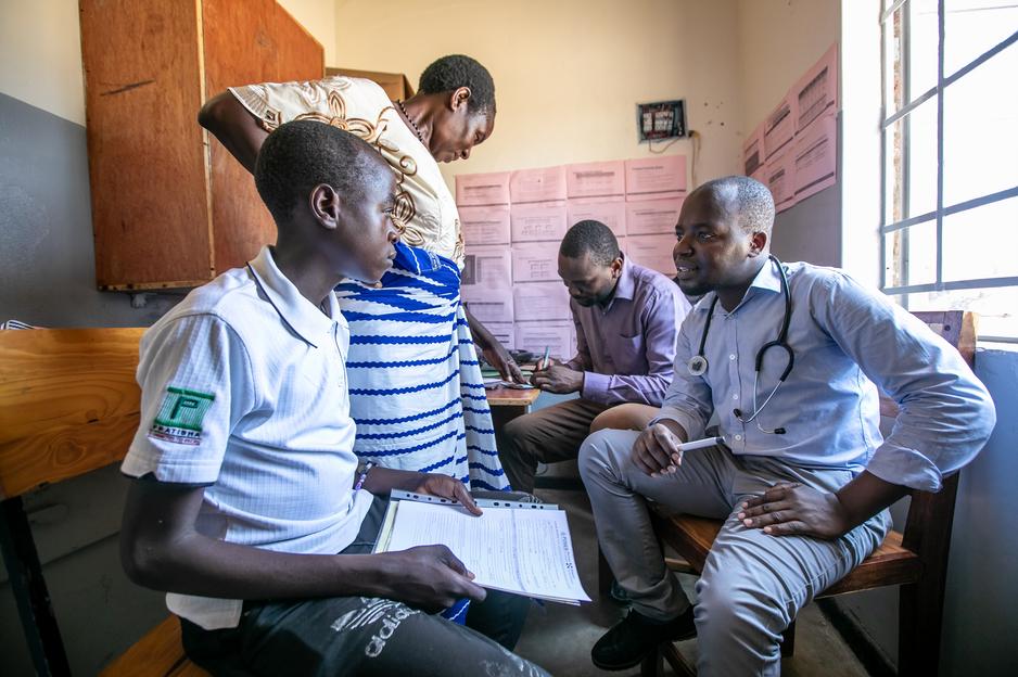 Kenwood Kumwenda chats with Kerefasi about his diabetes and checks his vitals, while clinical officer Medson Boti talks with Kerefasi's mother, Sofiya Simoni.