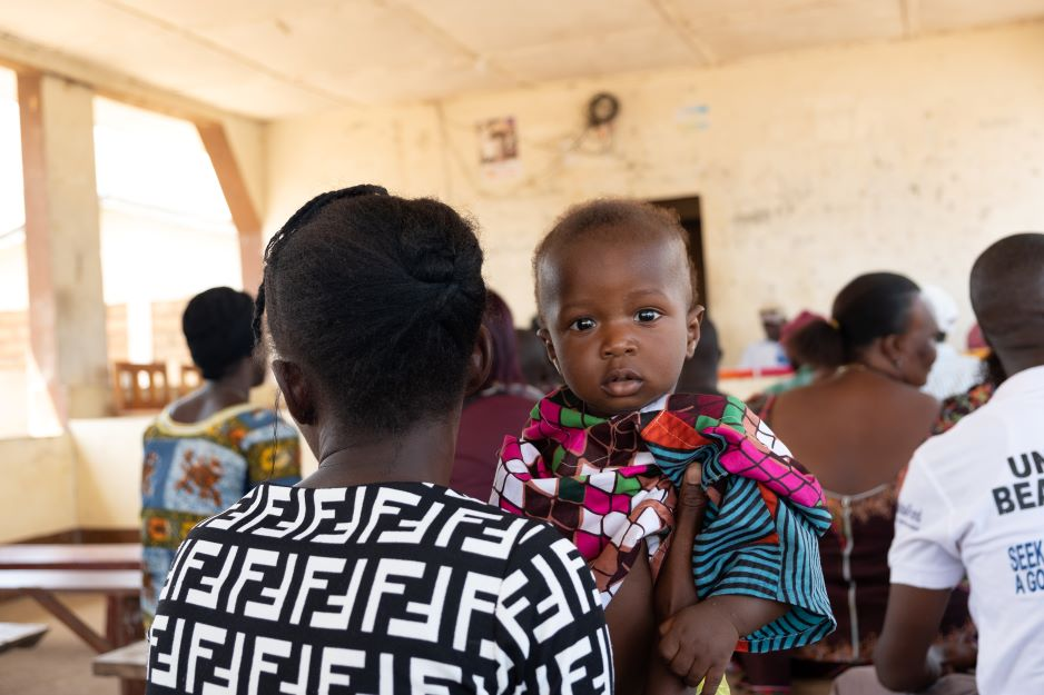 A mother and her child sit at the community outreach presentation