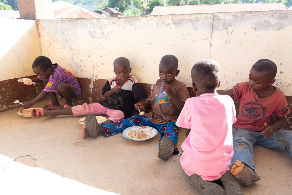 Children sit and eat to the side of the community outreach presentation