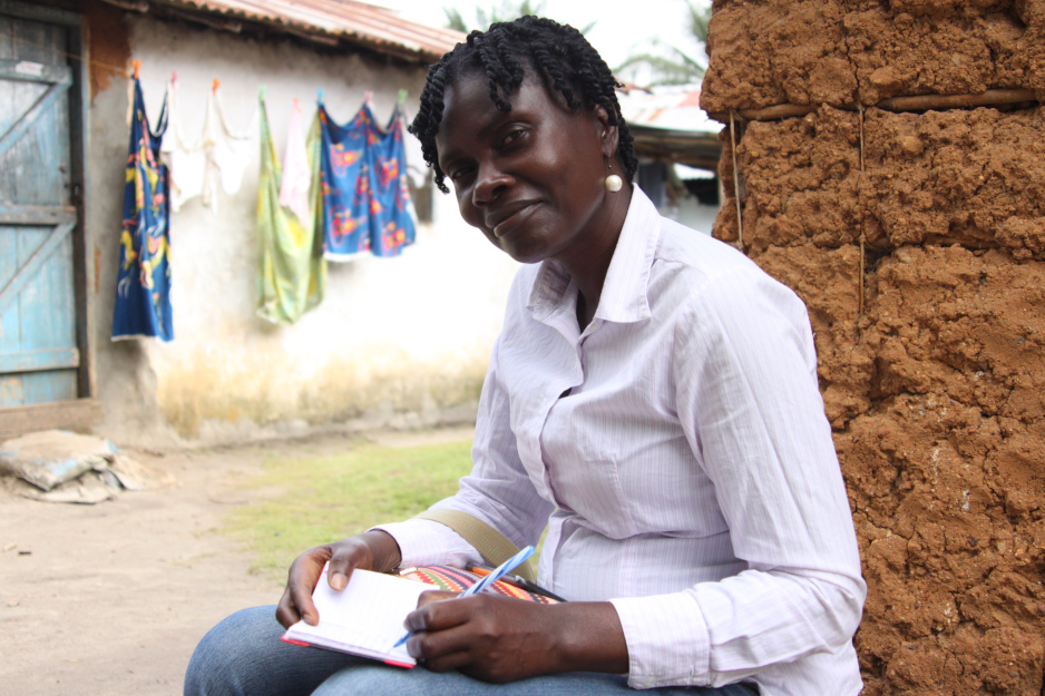 Community health worker Evelyn Toe records information about newborn Sheba Nyemade at the home of Sheba's mother, Cecile Johnson.