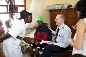 Dr. Paul farmer sits on a bed with a young male patient as they talk with a nurse