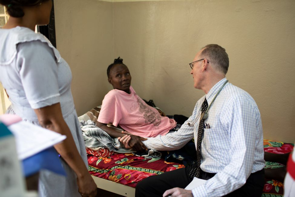 Dr. Farmer sits on the side a the bed of a female patient while they chat