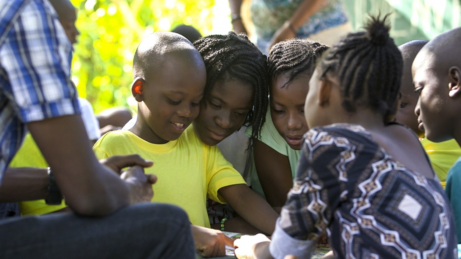 Samuel (from center left) and Betty share a book near the playground at Zanmi Beni, a children's home founded shortly after the devastating earthquake on January 12, 2010, in Port-au-Prince, Haiti.