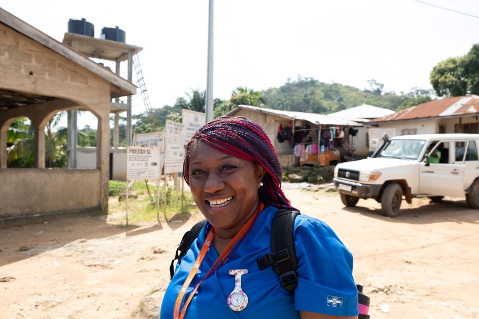 PIH Sierra Leone midwife Isata Dumbuya smiles while walking to a community outreach event