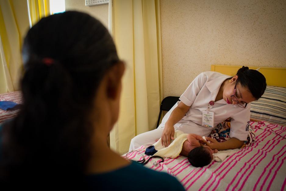 An obstetrics nurse checks in on a newborn.