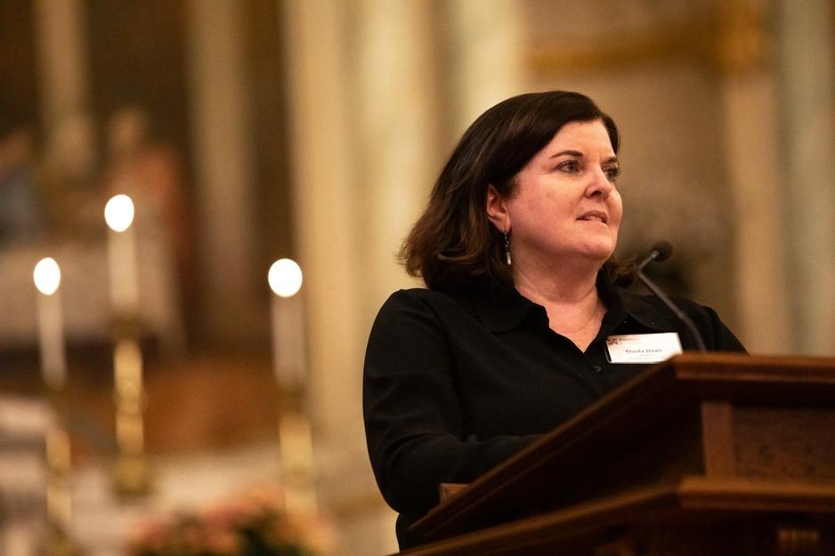 PIH CEO Dr. Sheila Davis stands speaking at a podium