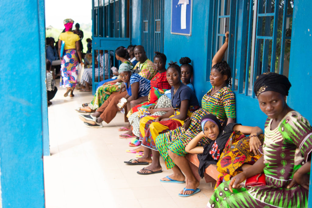 Pregnant woman sit and lay on benches outside Wellbody Clinic in Sierra Leone. Support from the Slaight Family Foundation will allow PIH to continue to improve health care for women and girls in Sierra Leone.