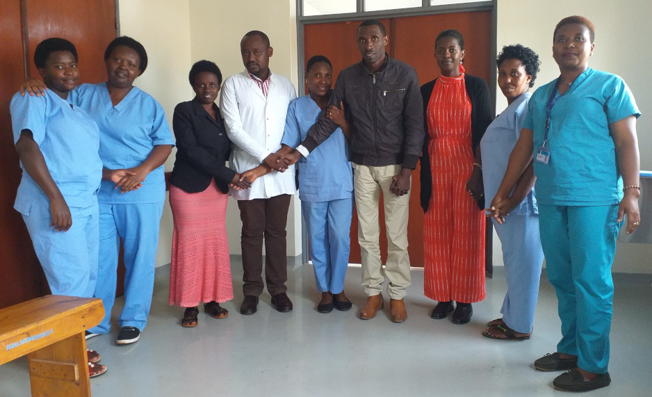 Nurse Andre Ndayambaje and colleagues stand holding hands