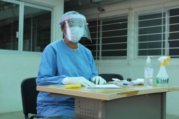 A nurse wearing PPE sits in a triage area as part of PIH's response to COVID-19 in Mexico
