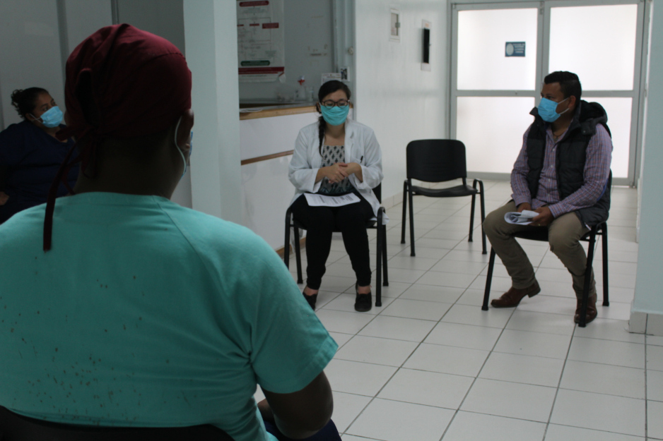 Staff sit spaced apart during a training as part of PIH's response to COVID-19 in Mexico