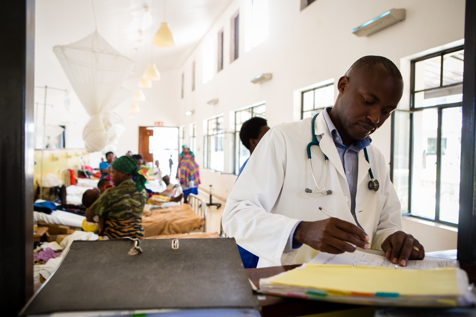 Dr. Cyprien Shyirambere, director of oncology for Inshuti Mu Buzima, as PIH is known in Rwanda, fills out paperwork after seeing patients for follow-up care in the oncology ward at Butaro District Hospital, in 2016. The hospital's radiotherapy cancer referral program saved more than 100 lives in a period from 2012-15, a recent study has shown. (Photo by Cecille Joan Avila/PIH)