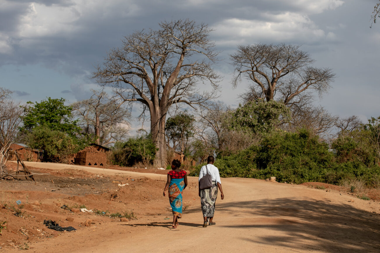 APZU Community Health Worker Grace Mgaiwa (right) walks with Eliza Kazembe (left) during a maternal health home visit near PIH-supported Lisungwi Community Hospital in Neno District, Malawi.