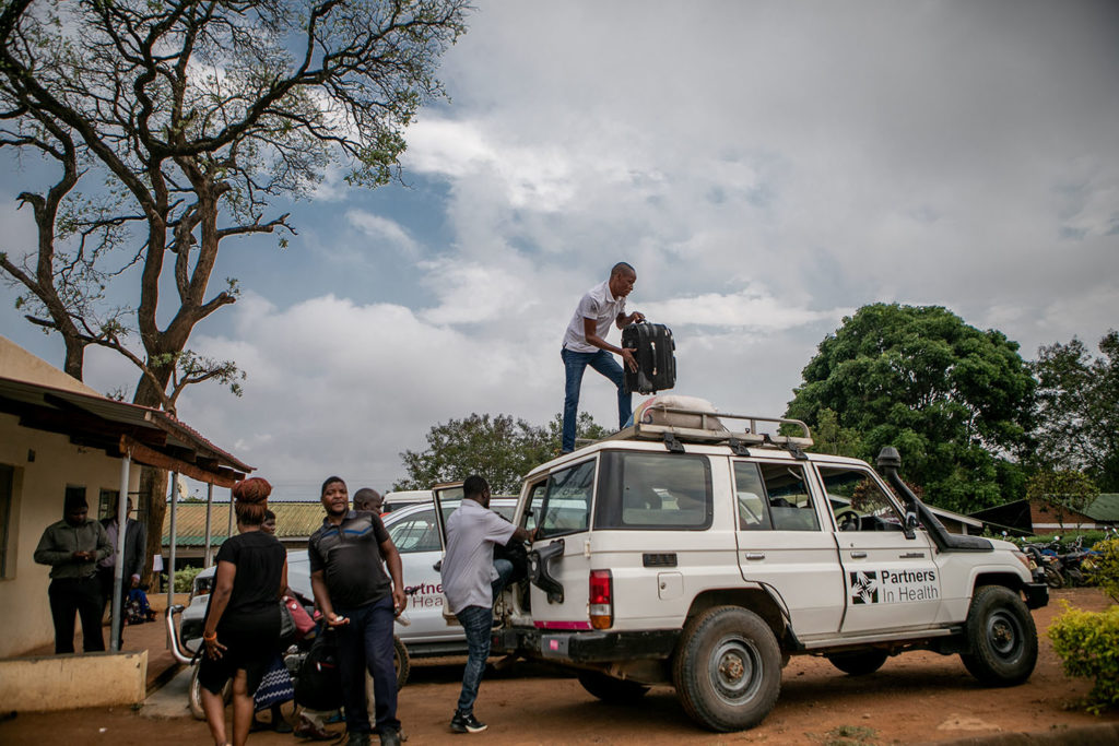Staff with Abwenzi Pa Za Umoyo, as PIH is known in Malawi, load a truck with social support items for patients and families in Neno District. (Photo by Karin Schermbrucker / Slingshot Media)
