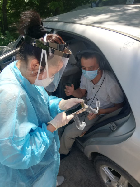 Dr. Merey Otepbergenova conducts a hearing test in the back of her personal vehicle in Almaty, Kazakhstan, as part of clinicians' efforts to reach severe TB patients safely during the COVID-19 pandemic. (Courtesy of PIH-Kazakhstan)