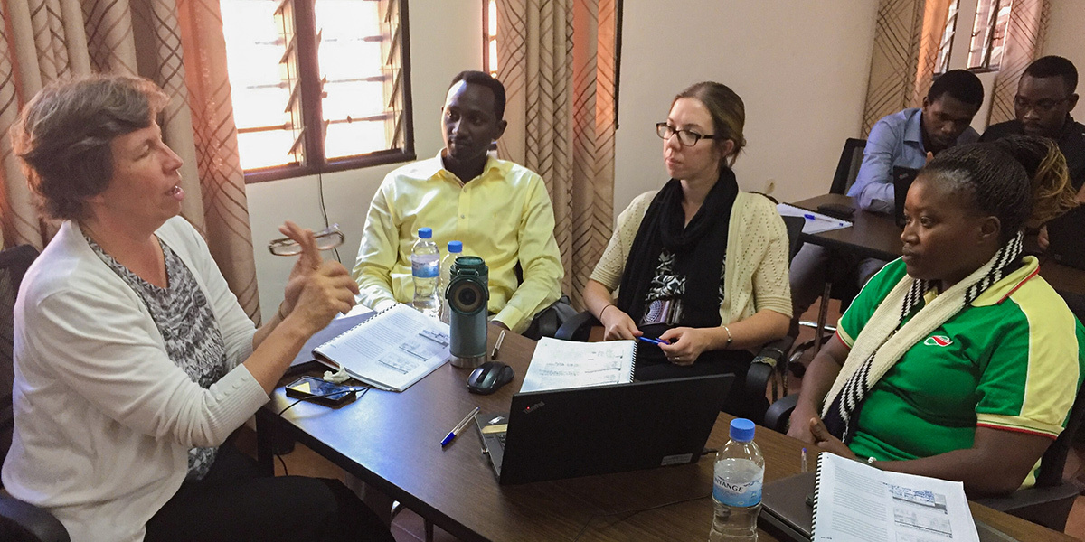 Dr. Ann Miller of Harvard Medical School (HMS), at left and senior mentor in a research training program hosted in Rwanda by HMS and Partners In Health, talks with (left to right) trainee Alain Ahishaliye of PIH; Katie Beck, then senior nutrition program manager for PIH in Rwanda; and trainee Marie Clarie Abimana, a registered nurse midwife and quality improvement advisor for PIH.