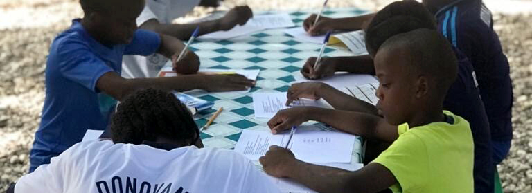 Students sit around a table in Haiti as they prepare to head back to school during COVID-19