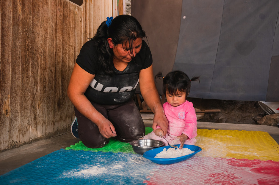 A caregiver knees on a mat next to a young child and then play with a plate of white flour as part of child development programming
