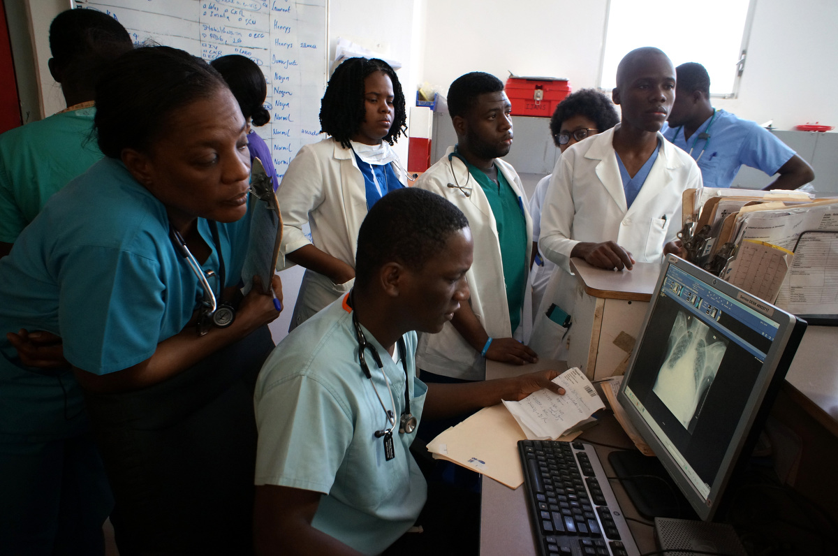 As part of University Hospital of Mirebalais' Residency Program Dr. Eliezer Dade sits at the computer reviewing a patient's chest x-ray in the emergency department.