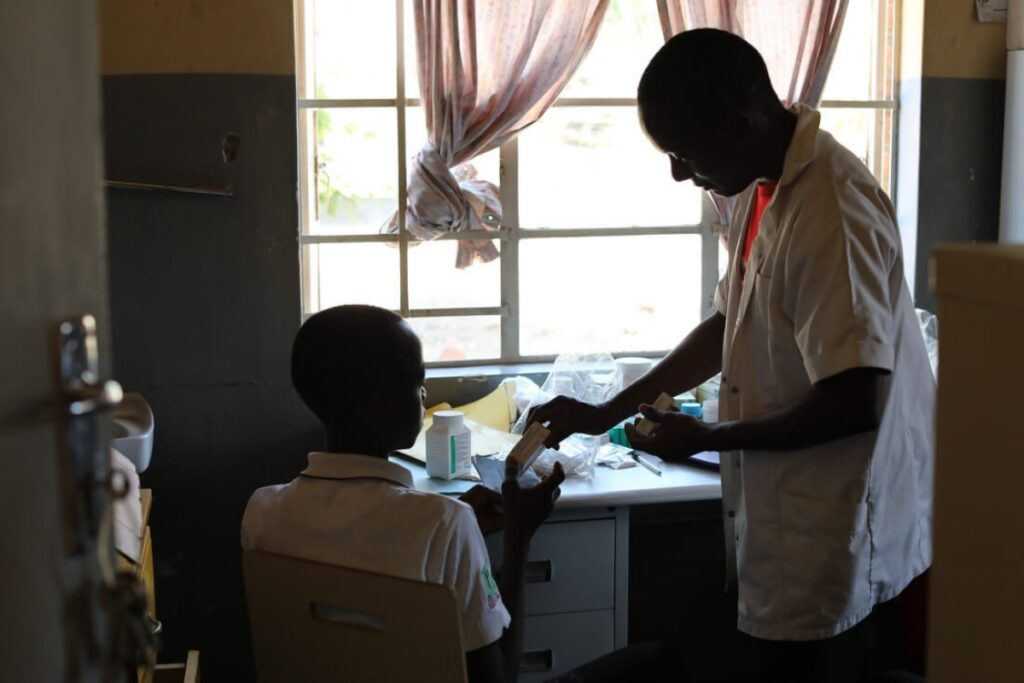 NCD nurse Victor Kaphaso advises teen diabetes patient Kerefasi Wiliyamu about his insulin, in the pharmacy room of PIH's Advanced NCD Clinic at Lisungwi Community Hospital in Neno District, Malawi.