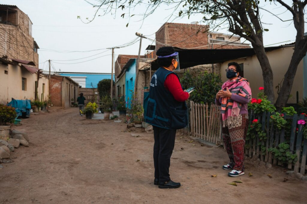 A staff member with Socios En Salud stands outside conducting a mental health screening with a patient in Peru