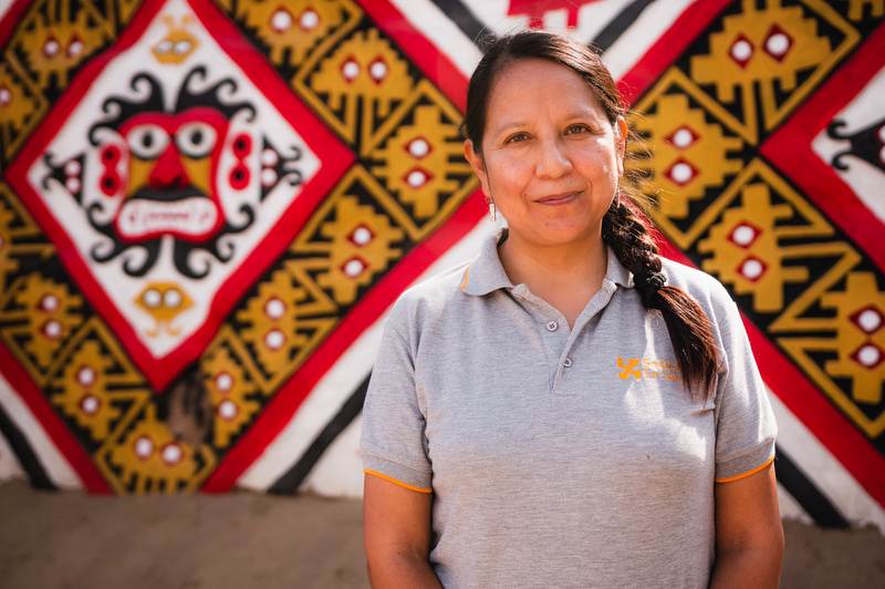 Carmen Contreras is director of mental health in Peru, stands in front of a brightly coloured patterned background.