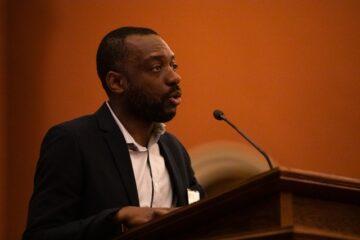 Dr. Patrick Ulysse stands speaking at a podium