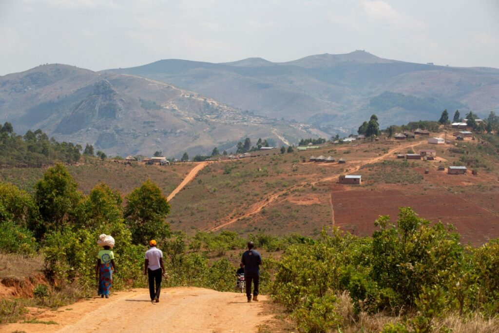 Agness Dyson (left) carries a bag of potatoes grown by her family as a gift to PIH caregivers in Neno, Malawi