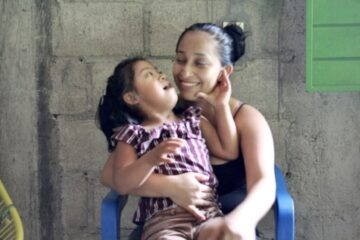 Smiling mother holding her daughter in their home in rural Chiapas, Mexico.